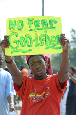 demonstrator: FERGUSON, MOUSA – AUGUST 15, 2014: Demonstrator holds sign at the site of destroyed Quick Trip after Police Chief Thomas Jackson release of the name of the officer that shot Michael Brown.