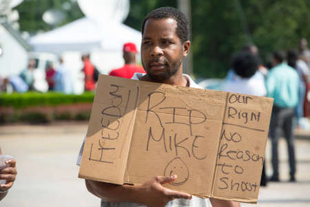 FERGUSON, MO/USA – AUGUST 15, 2014: Demonstrator holds sign at the site of destroyed Quick Trip after Police Chief Thomas Jackson release of the name of the officer that shot Michael Brown. Stok Fotoğraf - 34893544