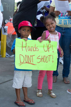 FERGUSON, MOUSA – AUGUST 15, 2015: Children at the Site of Quick Trip Hold sign after Police Chief Thomas Jackson release of the name of the officer that shot Michael Brown.
