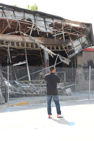 FERGUSON, MOUSA – AUGUST 15, 2014: Demonstrator in front of destroyed Quick Trip after Police Chief Thomas Jackson release of the name of the officer that shot Michael Brown.