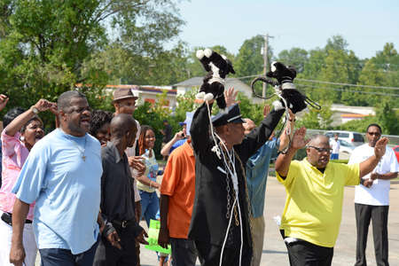 demonstrators: FERGUSON, MOUSA – AUGUST 15, 2014: Demonstrators at the site of destroyed Quick Trip react after Police Chief Thomas Jackson release of the name of the officer that shot Michael Brown.