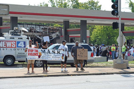 demonstrators: FERGUSON, MOUSA – AUGUST 15, 2015: Demonstrators at the Site of Quick Trip hold signs after Police Chief Thomas Jackson release of the name of the officer that shot Michael Brown.