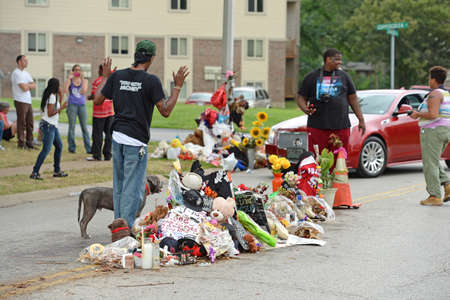 FERGUSON, MOUSA – AUGUST 30, 2014: A man raises hands at makeshift memorial where black teenager Michael Brown was shot to death by police in Ferguson, Missouri. Editorial
