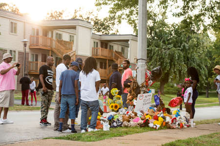 FERGUSON, MOUSA – AUGUST 30, 2014: A crowd gathers at makeshift memorial near where black teenager Michael Brown was shot to death by police in Ferguson, Missouri.