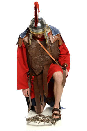 Roman soldier kneeling in front of crown of thorns over white background 写真素材
