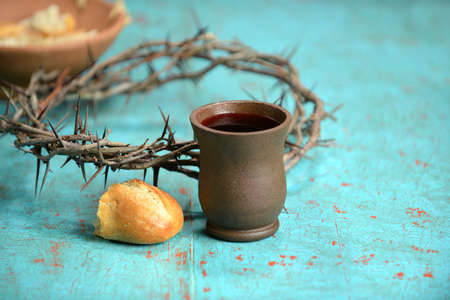 Bread, wine and crown of thorns on vintage table Stock Photo