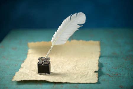 テーブルに羽とビンテージ紙とインクを書く 写真素材