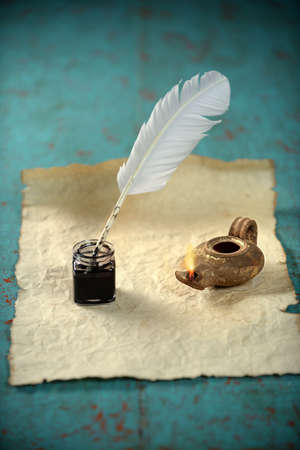 old times: Inkwell and ancient lamp over paper on vintage table Stock Photo