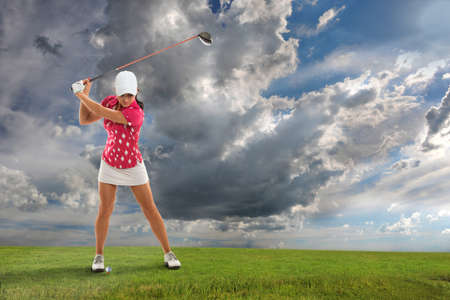 woman golf: Young woman playing golf on course Stock Photo