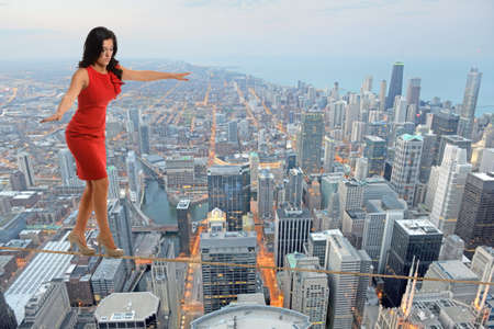 Businesswoman walking on tightrope with city in background