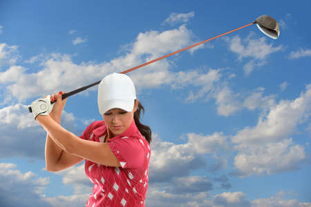 woman golf: Female golfer swinging golf driver during sunny day