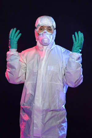pathologist: Man in Hazmat suit, protective gloves and goggles over dark background