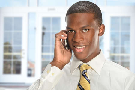 black business men: African American businessman using cellphone with office building in background