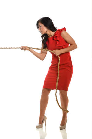 pulling rope: Young businesswoman pulling rope isolated over white background Stock Photo