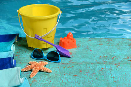 Summer time concept with toys, sunglasses, and starfish on painted wood Stock Photo