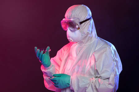 Scientist in protective Hazmat suit, gloves and goggles holding petri dish