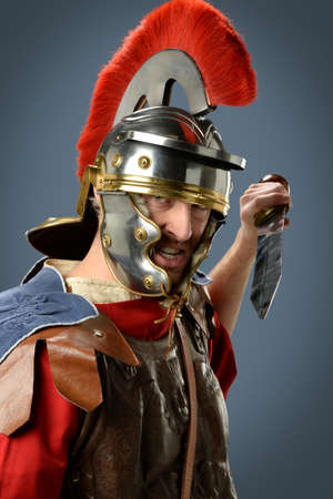 Roman soldier with sword over gray background
