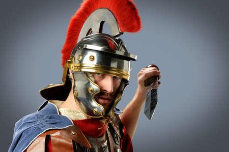 brandishing: Roman soldier brandishing sword over neutral background
