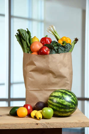 Fruits and vegetables in grocery bag and on wooden table Stock Photo