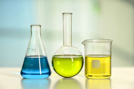 volumetric flask: Laboratory glassware on white table with window in background