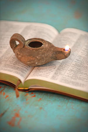Vintage oil lamp over open Bible on old table