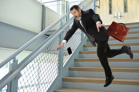 escalera: Hombre de negocios hispánico mayor que cae en las escaleras