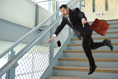 stairs interior: Senior Hispanic businessman falling on stairs