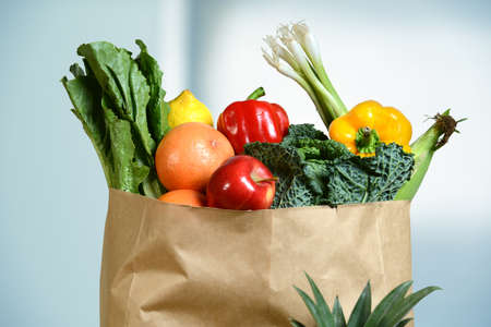 Assortment of fresh produce in grocery paper bag by window Stockfoto
