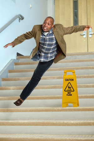 treacherous: African American businessman falling on stairs with yellow warning sign on steps