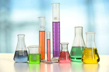 Laboratorium glaswerk met vloeistoffen van verschillende kleuren op witte tafel - met het knippen van weg op glas