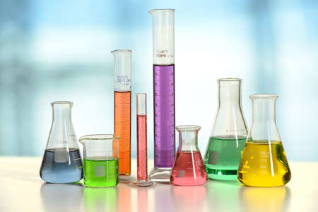 samples: Laboratory glassware with liquids of different colors on white table - With clipping path on glass