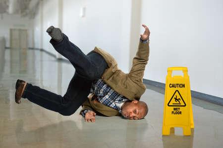 hombre cayendo: Hombre de negocios estadounidense que cae sobre suelo mojado en el cargo