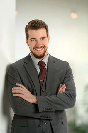 businessman in office: Portrait of young businessman leaning on office wall Stock Photo