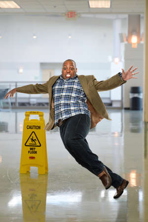 African American businessman slipping on wet floor inside office building