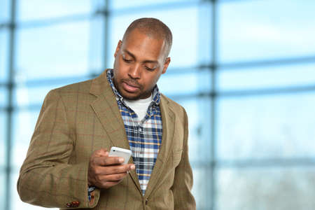 men talking: Young African American businessman using cellphone inside office building Stock Photo