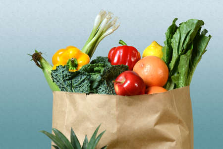Fresh: Assortment of fresh produce in grocery paper bag over gradient background
