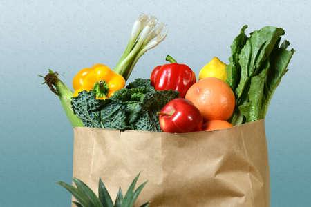 abarrotes: Surtido de productos frescos en la bolsa de papel de comestibles sobre fondo degradado Foto de archivo