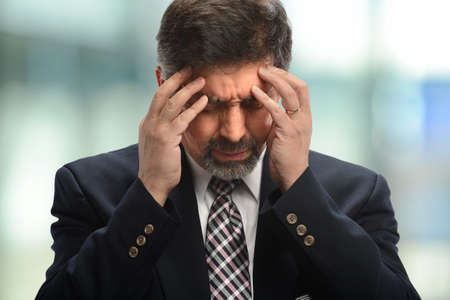 hombres maduros: Retrato de hombre de negocios hispanos bajo tensión en el interior del edificio de oficinas