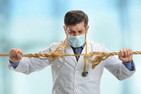 frayed: Doctor holding frayed rope inside hospital building Stock Photo