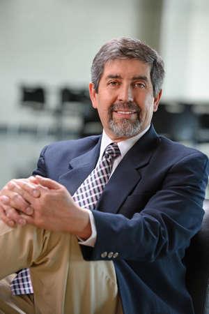 office man: Mature Hispanic businessman smiling inside office building Stock Photo