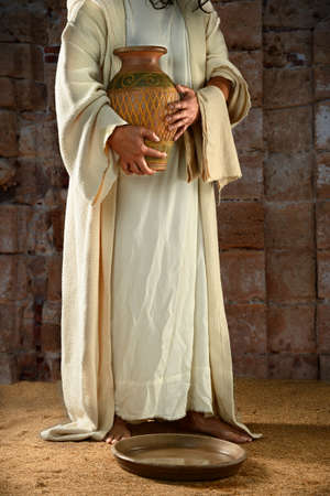 disciples: Jesus standing and holding water jar ready to wash the disciples feet Stock Photo