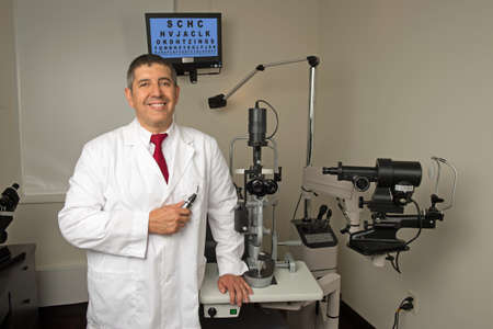 machines: Hispanic eye doctor in examination room surrounded by testing machines