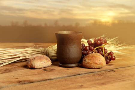 communion: Cup of wine, bread. grapes and wheat on vintage table with warm sunset in background