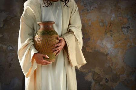イエスは、弟子たちの足を洗う準備ができて水の瓶を保持している手します。 写真素材 - 47035301