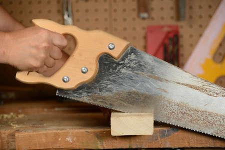 serrucho: Hombre cortando madera en la tienda con sierra de mano Foto de archivo
