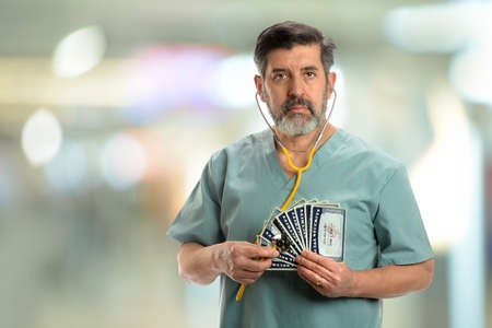 unsustainable: Social security concept. Senior doctor holding stethoscope to cards inside hospital building Stock Photo