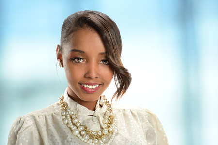 office environment: Portrait of young African American businesswoman smiling inside office environment Stock Photo