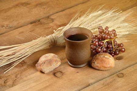 ワイン、ブラッド、小麦、ブドウ、太陽光フレア効果を持つヴィンテージのテーブルの上にカップと聖体拝領要素 写真素材