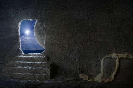 resurrección: tumba vacía de Jesús en la noche con cruces en el fondo Foto de archivo