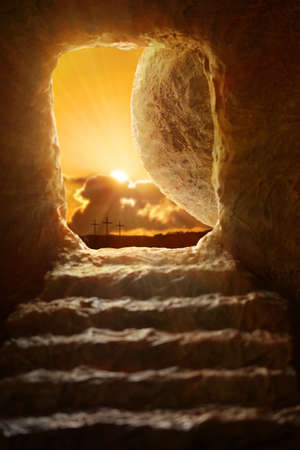 resurrected: Open tomb of Jesus with sun appearing through entrance - Shallow depth of field on stone